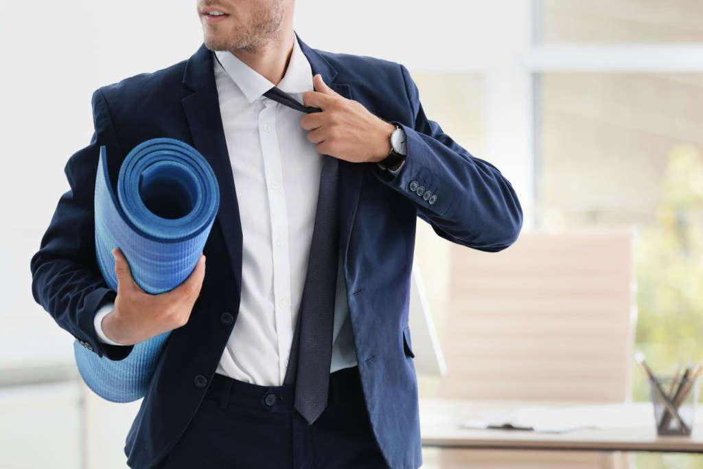 Mann im Anzug mit Yogamatte