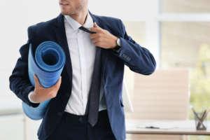 Mann im Anzug mit Yogamatte Yoga Kurse